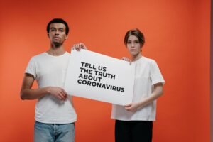 people holding a poster asking about the truth in coronavirus