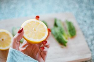 selective focus photography of person holding sliced lemon