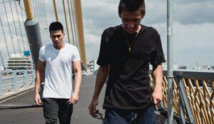 young asian men walking on asphalt bridge