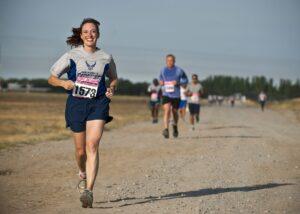 woman in gray crew neck shirt running on brown soil during daytime