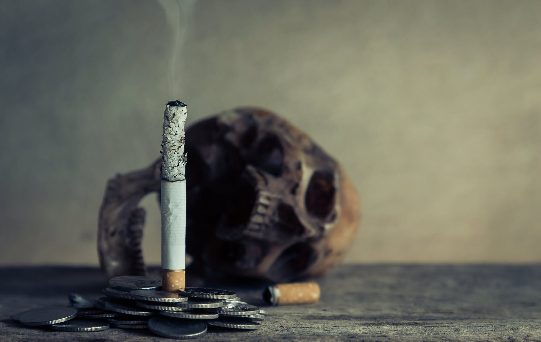cigarette stick on pile of coins