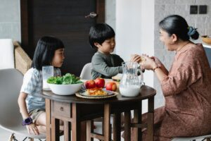 grandmother giving sandwich to asian grandson