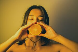 attractive woman with eyes closed holding orange slice against lips